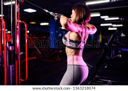 Athletic woman doing exercise for back, using machine, in gym - back view. #1363218074