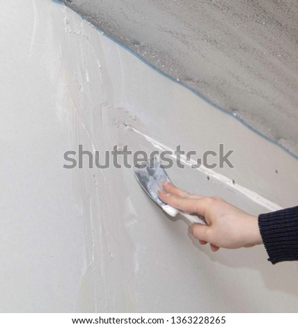 Worker aligns the walls with plaster. Repair in the house. #1363228265