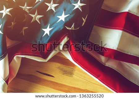 USA flag crumpled on wooden background, american banner with embroidered stars and stripes #1363255520