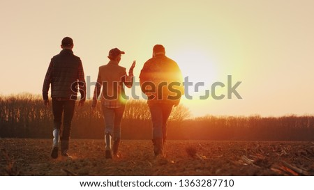 Three farmers go ahead on a plowed field at sunset. Young team of farmers #1363287710