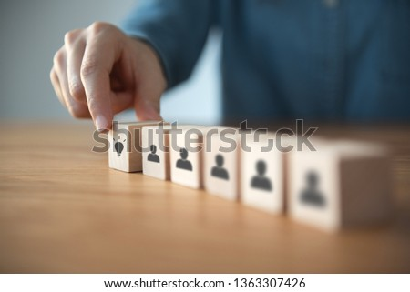 Closeup hand choosing wood cube with idea symbol in people icon. #1363307426