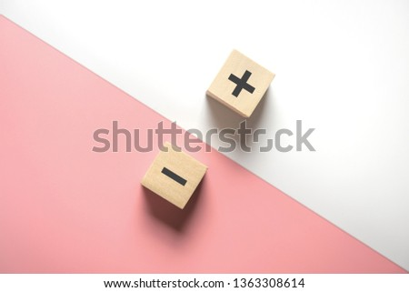 The concept of opposites, wood blog with plus and minus on white and pink background, flat lay, copy space, top view. #1363308614