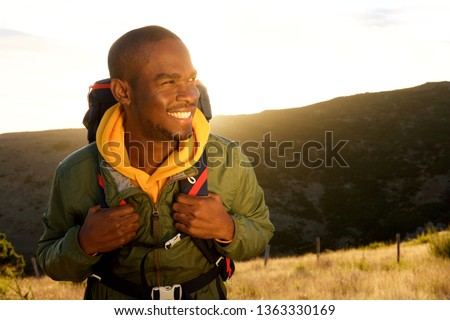 Close up portrait of handsome young african american man with backpack smiling with sunset in background #1363330169
