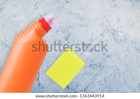 Household chemicals in the orange bottle and sponge. On the marble background tile. #1363443914