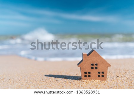 Small home model on sand beach with blue sky and white clouds background. Copy space of family lifestyle and business real estate concept. Vintage tone filter effect color style. #1363528931