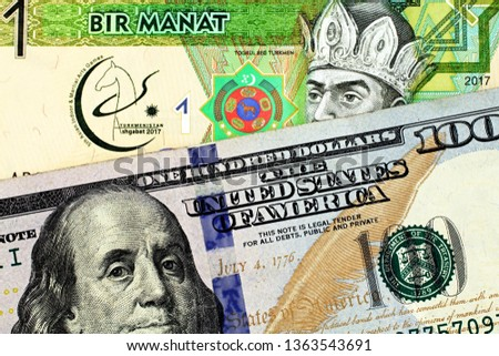A close up image of a one manat bank note from Turkmenistan with an American one hundred dollar bill in macro #1363543691