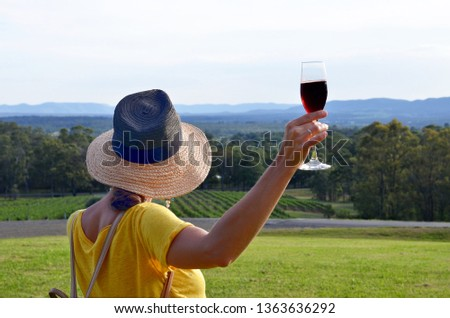 A woman wearing a hat and holding a glass with red sparkling wine admiring a beautiful landscape of winery fields, Hunter Valley, Australia