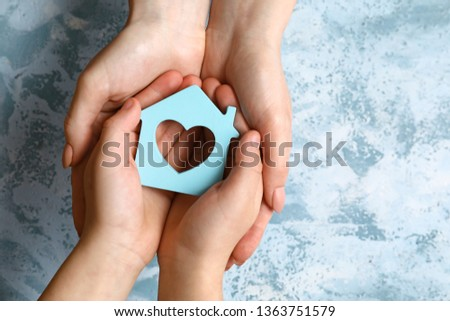 Hands of mother and child with model of house on color background. Concept of earthquake #1363751579