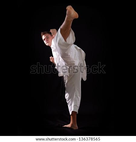 karate man with black belt posing, champion of the world on black background studio shot #136378565