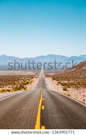 Idyllic vertical panorama view of an endless straight road running through the barren scenery of the American Southwest with extreme heat haze on a beautiful sunny day with blue sky in summer #1363901771