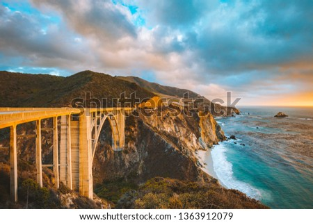 Scenic panoramic view of historic Bixby Creek Bridge along world famous Highway 1 in beautiful golden evening light at sunset with dramatic cloudscape in summer, Monterey County, California, USA Royalty-Free Stock Photo #1363912079