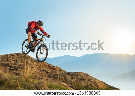 Cyclist in Red Jacket Riding the Bike in the Beautiful Mountains Down the Rock on the Sunrise Sky Background. Extreme Sport and Enduro Biking Concept. #1363938809