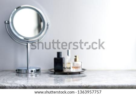 White marble table top can used for display or montage your products. Selective focus blurred white background. Vanity table makeup mirror perfume bottle spray.