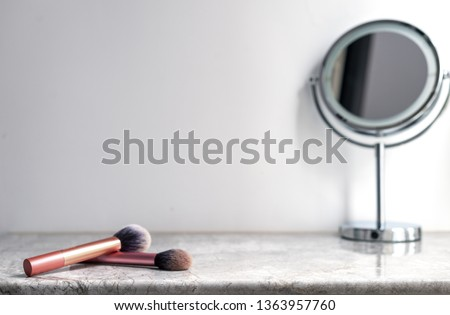 White marble table top can used for display or montage your products. Selective focus blurred white background. Vanity table with makeup brushes and  mirror.