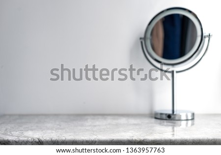 White marble table top can used for display or montage your products. Selective focus blurred white background. Vanity table with makeup vanity mirror.