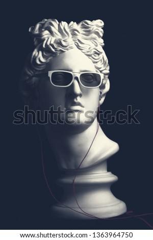 Statue. Earphone. Isolated. Gypsum statue of Apollo's head. Man. Creative. Plaster statue of Apollo's head in earphones and white sunglasses. Apollo Belvedere. Artwork #1363964750