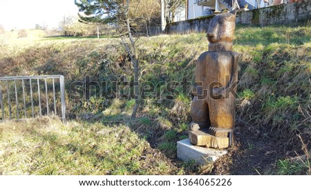 Bear wood statue on grass Royalty-Free Stock Photo #1364065226