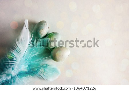 Background for Easter. Decorative Easter eggs of blue color, decorated with colored feathers on a blue background. Bokeh effect. Copy space. #1364071226