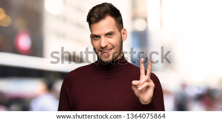Man with turtleneck sweater smiling and showing victory sign in the city #1364075864