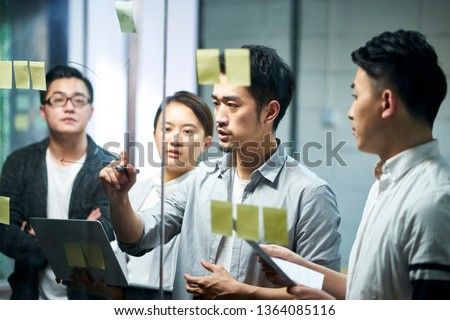 young asian entrepreneur of small company drawing a diagram on glass during team meeting discussing and analyzing business situation in office. #1364085116