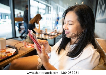 Woman use smartphone tablet in restaurant #1364087981