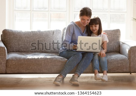 Mother and daughter sitting on couch spends time in living room at home having fun together using computer apps, browsing internet, watching cartoon online, mom teach kid electronic device use concept