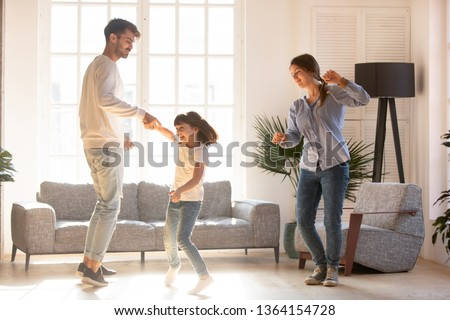 Family mother father and preschool adorable daughter in living room moving dancing to music little girl holding father hand having fun enjoy time with parents at home. Funny leisure activities concept #1364154728