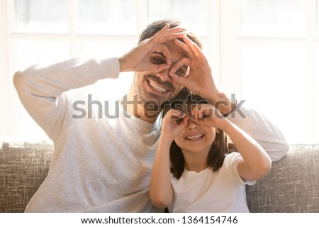 Pretty family father adorable daughter sitting on sofa do funny faces making with fingers eyewear shape like glasses looking through binoculars, have fun with child free time play tricks fool concept #1364154746