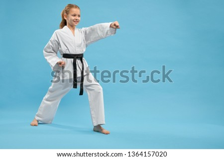 View from side of cheerful female fighter standing in stance and punching with hand in studio. Smiling girl wearing kimono practising karate and jujitsu on blue isolated background. Concept of sport. #1364157020