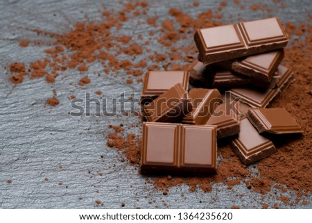 Dark or milk organic chocolate pieces and cocoa powder on dark concrete backgound #1364235620