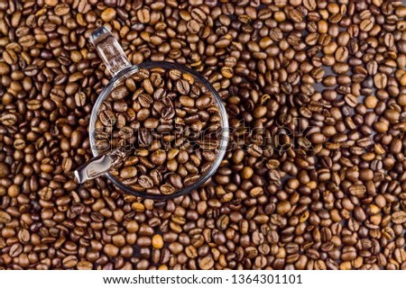 Roasted coffee beans in a glass cup. Brown coffee grains. Background texture. Closeup. Natural background. Can be used as a background. Blurred background, selective focus.  #1364301101