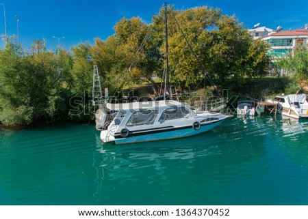Alanya, Turkey - October 05, 2018. A small speedboat moored at the pier along the coast against a blue sky. Photos of the ship from the sea. The concept of summer holidays, sports, tourism #1364370452