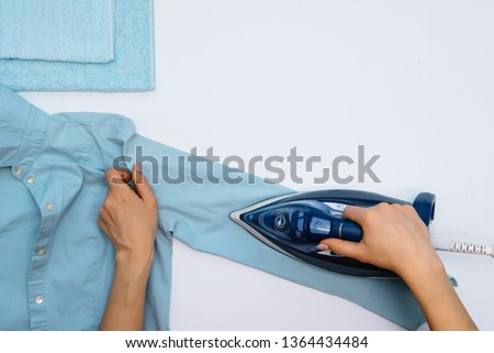 Female hand ironing clothes top view isolated on white background. Young woman with iron ironing man's shirt seen from above during housework. Blue iron on white table. #1364434484