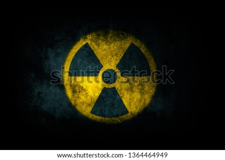 Nuclear energy radioactive (ionizing atomic radiation) round yellow symbol shape painted on massive concrete cement wall texture dark background. Nuclear radiation or radioactive alert warning danger. #1364464949