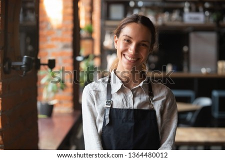 Head shot portrait successful mixed race businesswoman happy restaurant or cafeteria owner looking at camera, woman wearing apron smiling welcoming guests having prosperous catering business concept #1364480012