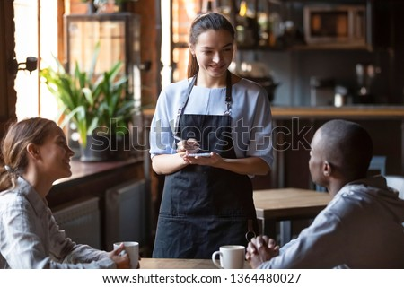 Waitress female welcoming diverse cafeteria pub guests african guy mixed race girl making order waiting staff writing wishes on notepad. Good service dining time, friends meets in public place concept #1364480027