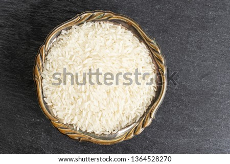 Lot of whole white jasmine rice grains in old iron bowl flatlay on grey stone #1364528270