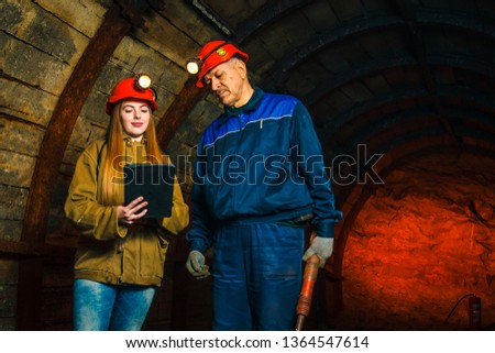 A beautiful young girl in a red helmet and with a electronic tablet in her hands is standing with a miner in a coal mine. Business plan discussion. #1364547614