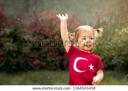Portrait of happy little kid, cute baby toddler with Turkish flag t-shirt wave her hand. Patriotic holiday. Adorable child celebrates national holidays. Blur background with copy space for text. #1364565458