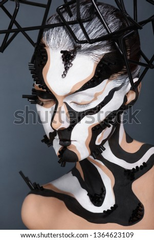 Female model with creative abstract makeup in futuristic hat.