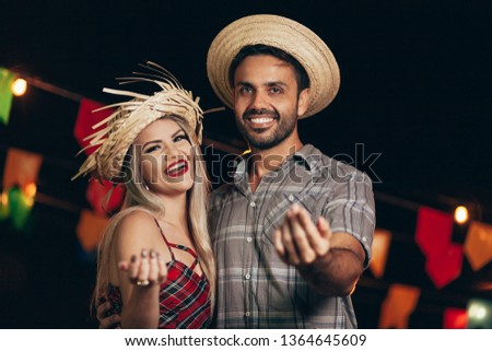 Brazilian couple wearing traditional clothes for Festa Junina - June festival - dancing under the night sky #1364645609