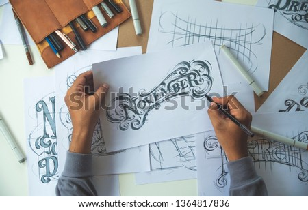 Typography Calligraphy artist designer drawing sketch writes letting spelled pen brush ink paper table artwork.Workplace design studio. #1364817836