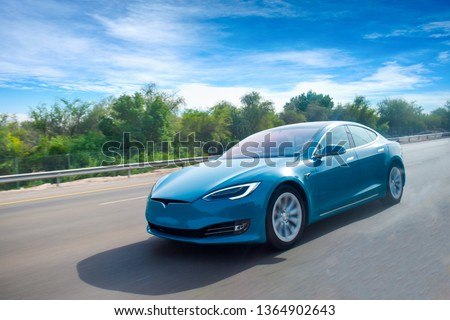 A blue coloured electric car cruising on highway,with clear blue sky.green energy concept.Have space for text. Royalty-Free Stock Photo #1364902643