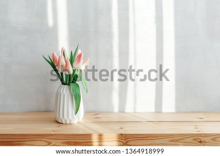 Light pink tulips in a white geometric ceramic vase stand on a wooden table near grey wall. Bouquet of flowers in the morning sun beams. #1364918999