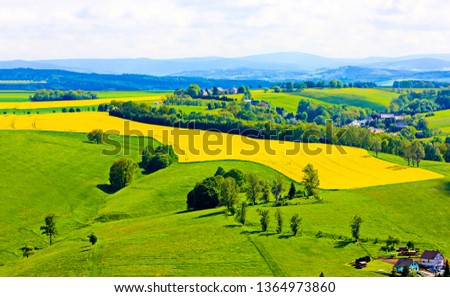 Agriculture farm hills valley landscape. Farm field in mountain hills panorama. Agriculture mountain farm hills view. Agriculture mountain farm hills scene #1364973860