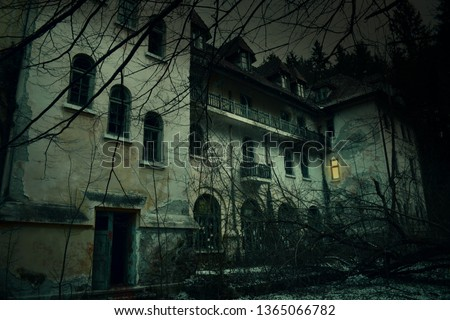 Old abandoned mansion in mystic spooky forest. The ancient haunted house of the crime scene with dark horror atmosphere and creepy details Royalty-Free Stock Photo #1365066782