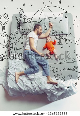 No matter what the weather. Top view photo of young man and his child sleeping in a big white bed. Dreams concept. Painted dream about rain, weatherness, walk, umbrella, autumn, father's protection.