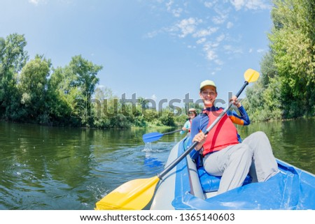 Happy family kayaking on the river. Active girl with her mother having fun enjoying adventurous experience with kayak on a sunny day during summer vacation #1365140603