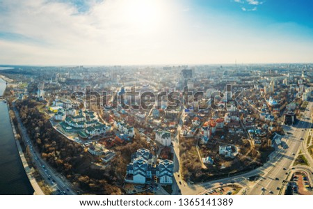 Aerial panorama of city from above, high angle view to urban buildings, roads with cars, skyline in sunny spring day, drone shot, toned #1365141389