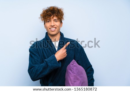 Young african american man in pajamas pointing finger to the side #1365180872